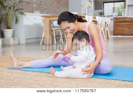 Happy mother and baby daughter sitting on exercising mat at home