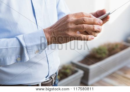 Mid section of man using smartphone at home in the garden
