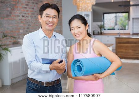 Happy couple using tablet and holding mat at home