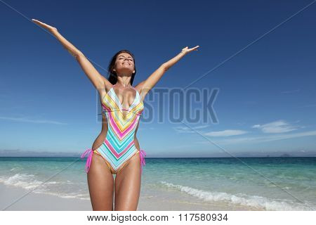 Beautiful happy woman in bikni with raised hands on tropical beach
