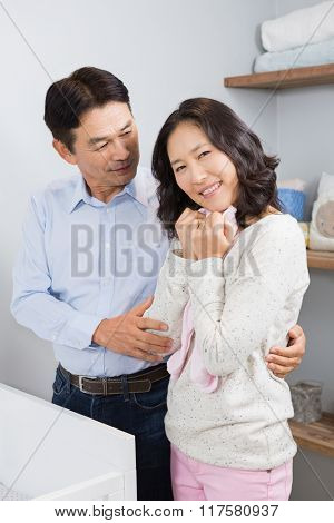 Happy couple holding pink onesie near a crib