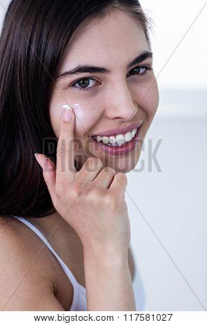 Brunette applying face cream in bathroom