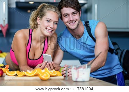 Healthy couple looking at smartphone in the kitchen