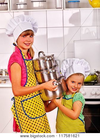 Children wearing chef hat holding group pans at kitchen.