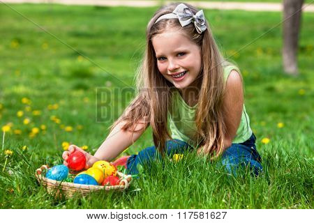 Happy beautiful child find easter egg outdoor. Girl lying on green spring grass.