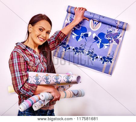 Happy woman going to glues wallpaper at home.