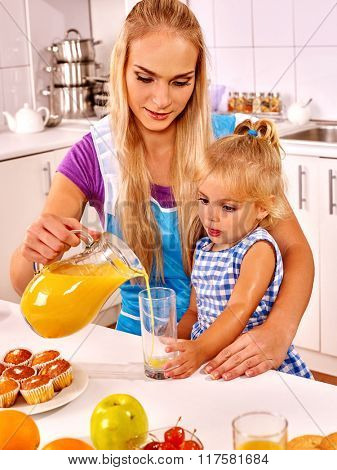 Mom pours juice her daughter at kitchen.