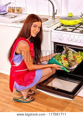 Happy woman wearing red apron prepare fish in oven.