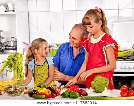 Big family cooking at kitchen. Grandfather preparing food with his children.