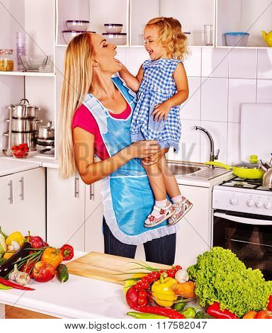 Mother feed her little daughter child at kitchen.