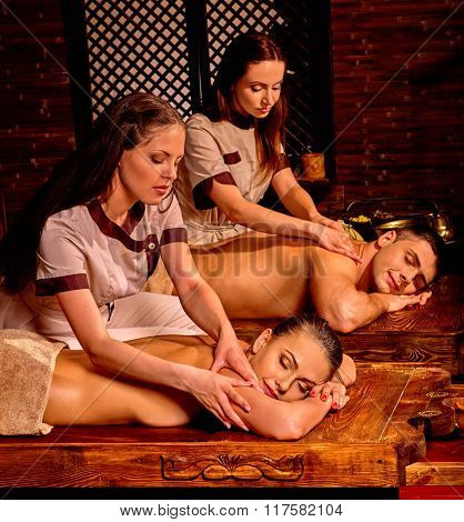 Young family having oil Ayurveda spa treatment in honeymoon.