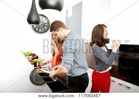 Brother and sisters cooking meal together.