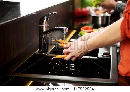 Woman washing carrots.