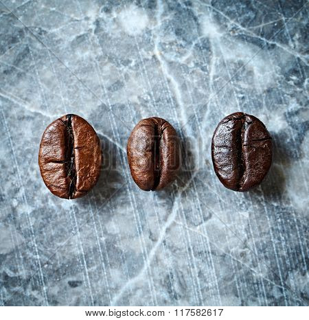 Three types of coffee beans on a marble background
