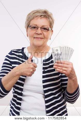 Happy Senior Female Holding Currencies Dollar And Showing Thumbs Up, Concept Of Financial Security I