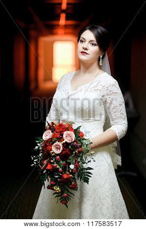 Brunette bride with bouquet standing in hotel hallway, tunnel light.