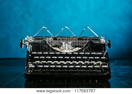 Old vintage typewriter with dark blue background