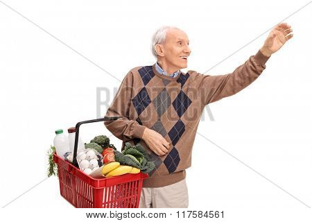 Cheerful senior holding a shopping basket and reaching for something isolated on white background