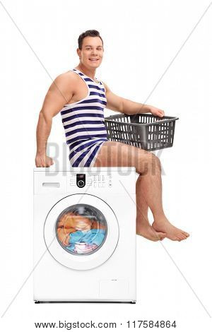 Young man in a stripped underwear sitting on a washing machine and holding an empty laundry basket isolated on white background