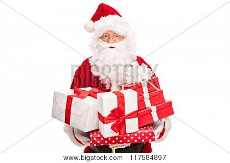 Studio shot of Santa Claus holding a bunch of presents and looking at the camera isolated on white background