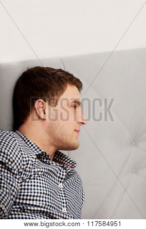 Handsome young adult man in bedroom.