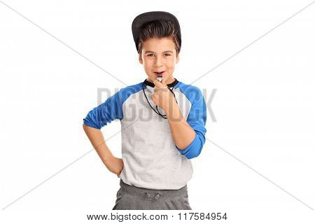 Cheerful boy in sportswear blowing a whistle and looking at the camera isolated on white background