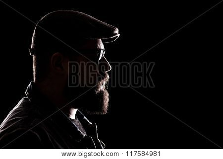 Profile shot of a hipster with thick beard and a beret on a black background