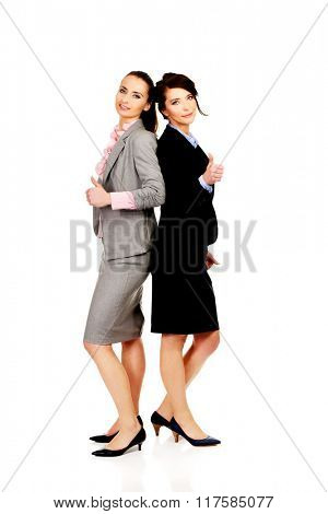 Two women in office outfits with thumbs up.