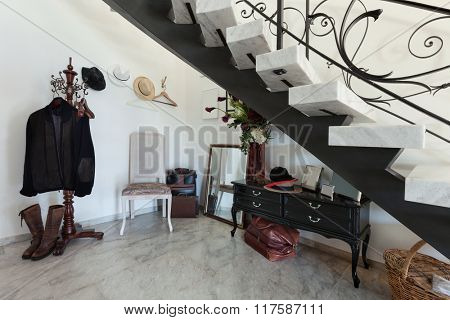 Interior of an house, detail under stairs, hangers and bags