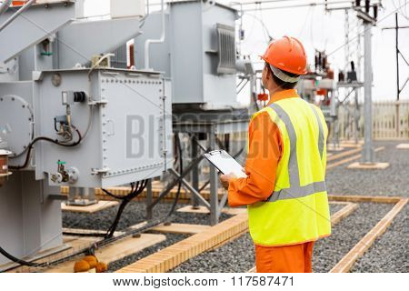 back view of electricity company substation worker