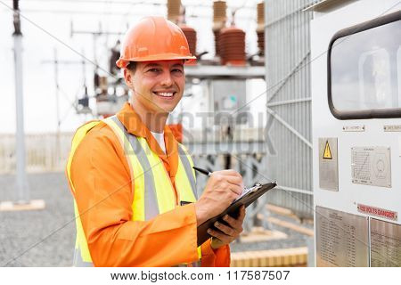 portrait of happy young electric worker taking transformer readings