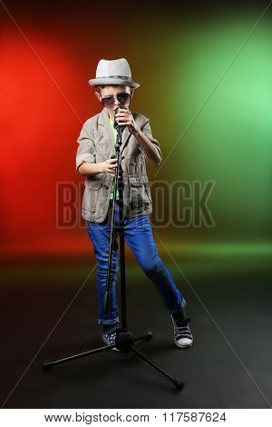 Little boy singing with microphone on a bright background