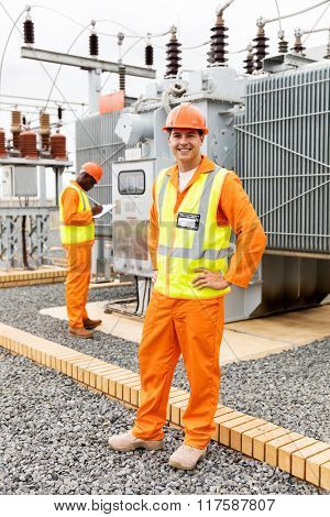 happy electrical engineer in substation with colleague on background