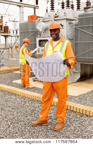 portrait of handsome african electric engineer with blueprint at substation