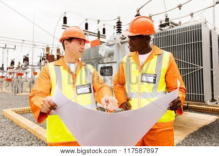 male engineers discussing blueprint at electrical substation