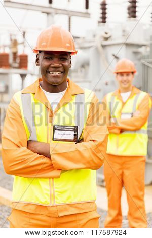 smiling senior african technician with colleague on background in substation