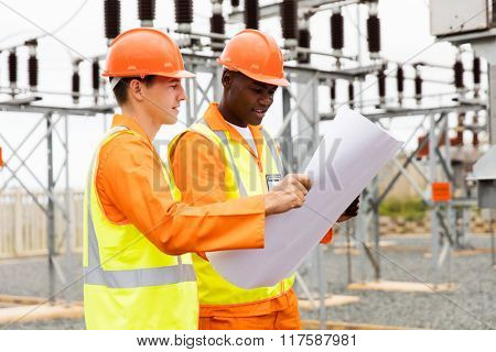 electric engineers discussing blueprint in substation