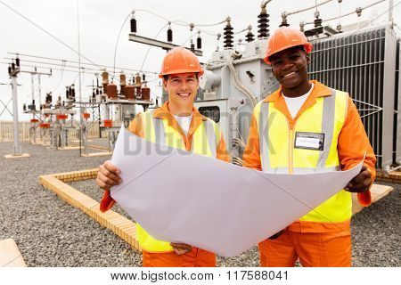 smiling electricians holding blueprint at substation