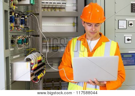 technician checking machine status on laptop computer