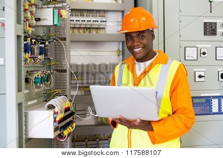 cheerful african american electrical engineer working on laptop