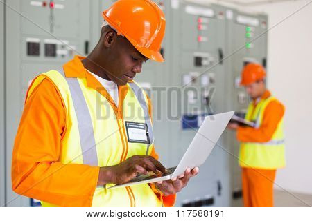 black technical worker using laptop with colleague on background