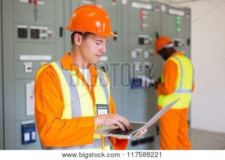electrical worker working on laptop with colleague on background
