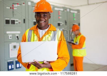 portrait of afro american engineer using laptop computer in control room