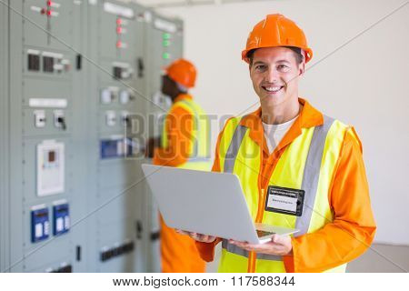 portrait of modern young electrician with laptop computer