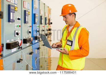 experienced electrician working on laptop in substation