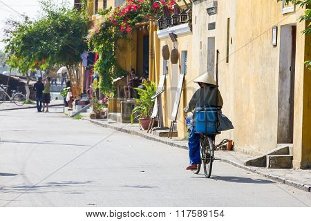 Old woman in conical hat is riding bicycle down the street of Hoi An Ancient Town