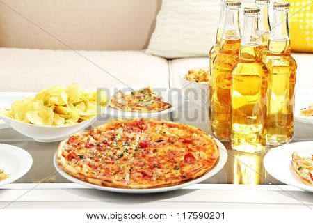 Table at home with pizza and drinks for friends