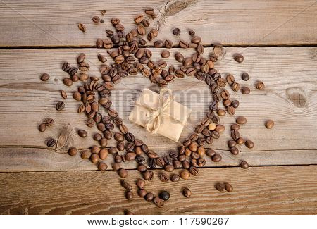 Frame- Heart From Coffee Beans And Small Parcel Inside It On  Wooden Table