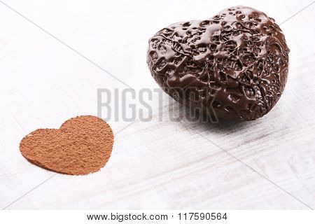 Sweet heart shaped candies on white wooden background