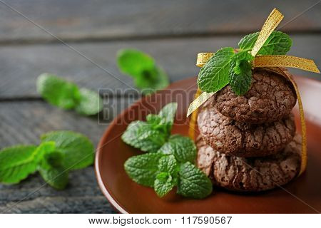 Chocolate chip cookie with yellow stripe and mint in plate, closeup